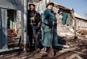 A couple stand outside their home in Debaltseve, Ukraine