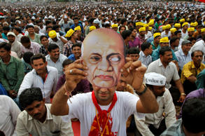 A member of Patel community holds a mask of Indian freedom fighter Sardar Vallabhbhai Patel at a rally in Ahmadabad