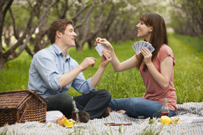 Couple playing cards in a park. Mike Kemp/Getty Images