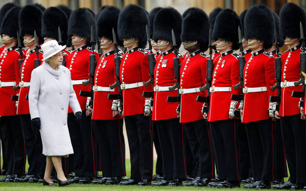 Britain's Queen Elizabeth inspects the guards during the ceremony to present new colours to the 1st Battalion and No. 7 Company the Coldstream Guards at Windsor Castle, England, Thursday May 3, 2012.