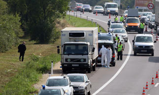 Police stand near a truck containing the bodies of migrants on the shoulder of a highway near Parndorf south of Vienna, Austria, Thursday, Aug 27, 2015.