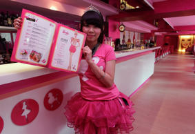 "A waitress poses with a menu during the media preview of a Barbie-themed cafe in Taipei January 30, 2013. The 660-square-metre ""Barbie Cafe"", fashioned with Mattel's barbie dolls themed decor and food dishes, will open January 31 along Taipei's Zhongxiao Dunhua shopping belt."