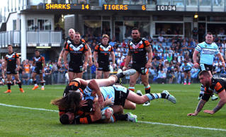 Michael Ennis of the Sharks scores a try in the tackle of Aaron Woods and James Tedesco of the Tigers.