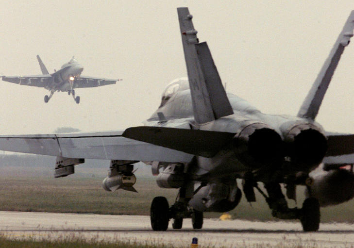 A Canadian F-18 Hornet fighter jet lands while another prepares to take off from the Italian-American NATO air base in Aviano in this October 12, 1998 file photo.