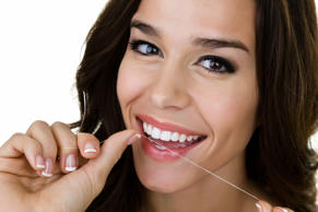 Closeup of a woman flossing her perfect teeth