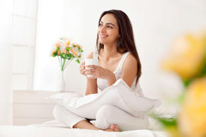 A happy young woman having a cup of coffee on her bed in the morning.