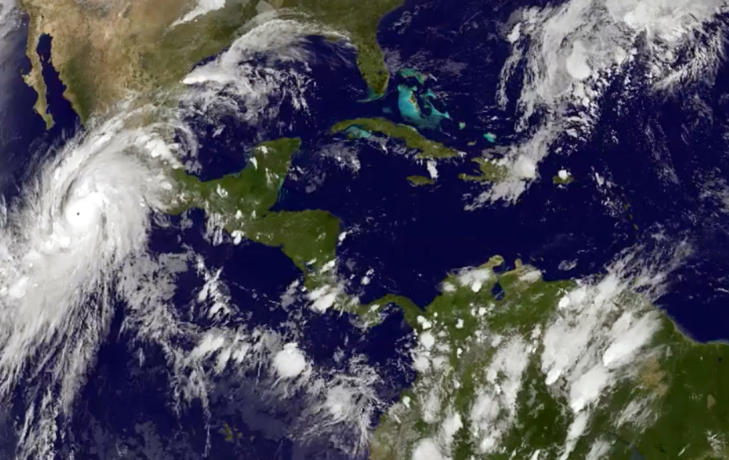 This satellite image taken at 8:45 p.m. EDT on Thursday, Oct. 22, 2015, and released by the National Oceanic and Atmospheric Administration shows Hurricane Patricia, left, moving over Mexico's central Pacific Coast.