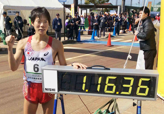 REFILE - ADDING DISCLAIMER Japan's Yusuke Suzuki poses next to a electric time board showing his record after breaking the 20-kilometer race walk world record at the IAAF Race Walking Challenge, in Nomi, central Japan, in this photo taken by Kyodo March 15, 2015. Suzuki won the event with a time of 1 hour, 16 minutes, 36 seconds, establishing a new world record, local media reported.
