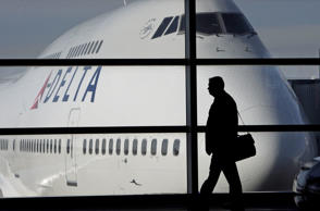 In this Jan. 21, 2010 file photo, a passenger walks past a Delta Airlines 747 aircraft in McNamara Terminal at Detroit Metropolitan Wayne County Airport in Romulus, Mich. Fares are higher, demand is up and the airlines have established a steady revenue stream from add-on fees for baggage, pillows and food.