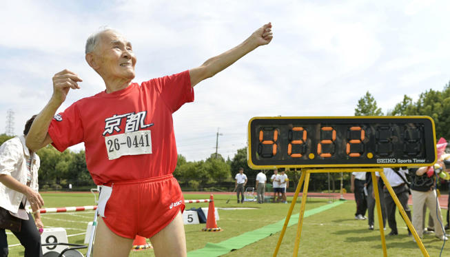 105-year-old Japanese Hidekichi Miyazaki poses like Jamaica's Usain Bolt in front of an electric board showing his 100-metre record time of 42.22 seconds at an athletic field in Kyoto, Japan, in this photo taken by Kyodo September 23, 2015. Japanese centenarian Hidekichi Miyazaki set a record as the world's oldest competitive sprinter this week, one day after turning 105, but said he was disappointed at falling short of his own personal best. Picture taken September 23, 2015.