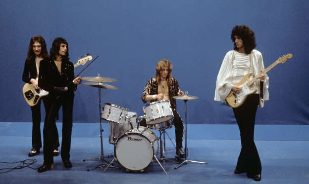 Slide 1 of 27: L-R John Deacon, Freddie Mercury, Roger Taylor and Brian May of Queen perform 'Killer Queen' on Top Pop TV show on 22nd November 1974 in Hilversum, Netherlands. Brian May plays a Fender Stratocaster guitar. (Photo by Gijsbert hanekroot/Redferns)