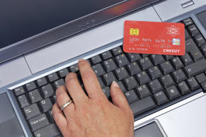 woman typing in her credit card details on a laptop computer. The card is a mock-up made by mysel