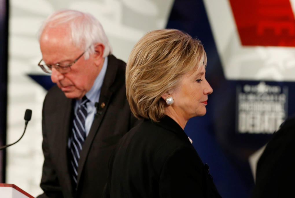 Democratic U.S. presidential candidate former Secretary of State Hillary Clinton walks past fellow candidate and Senator Bernie Sanders during a break at the second official 2016 U.S. Democratic presidential candidates debate in Des Moines, Iowa, November 14, 2015.