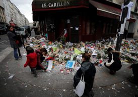 People lay flowers and candles in front of the restaurant Le Carillon, one of the establishments targeted in Friday's gun and bomb attacks, in Paris, Monday, Nov. 16, 2015. French police raided more than 150 locations overnight as authorities released the names of two more potential suicide bombers involved in the Paris attacks— one born in Syria, the other a Frenchman wanted as part of a terrorism investigation. (AP Photo/Frank Augstein)