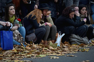 Members of the public grieve as they sit opposite the main entrance of Bataclan concert hall as French police lift the cordon following Fridays terrorist attacks on November 16, 2015 in Paris, France. A Europe-wide one-minute silence was held at 12pm CET today in honour of at least 129 people who were killed last Friday in a series of terror attacks in the French capital.