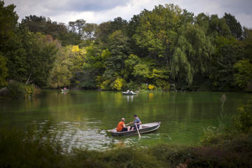 People row boats on The Lake during a warm October afternoon as the first hints of fall colours appear on the trees in New York's Central Park in Manhattan, October 8, 2015.