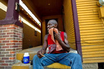 "Arthur Posey wipes sweat from his face while he sits on his front porch on Rosaline Street Wednesday, Aug. 3, 2011, in Houston. Posey sits on his porch everyday because he doesn't have air conditioning. ""I'm just trying to stay cool,"" he said."