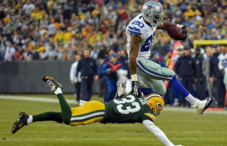 Dallas Cowboys running back Darren McFadden (20) jumps over Green Bay Packers safety Micah Hyde (33) for a first down in the first quarter at Lambeau Field on Dec. 13, 2015 in Green Bay, Wisc.