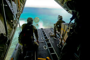 In this Dec. 8, 2015 photo provided by the U.S. Air Force, Cpl. Teome Matamua and Sgt. Phillip McIllvaney of the Australian Army 176th Air Dispatch Squadron loadmasters deliver a package to the island of MogMog in the Federated States of Micronesia as part of Operation Christmas Drop. Australian, Japanese and U.S. air force planes are dropping food and toys on remote atolls in the Pacific as part of the U.S. military's longest-running humanitarian relief mission.