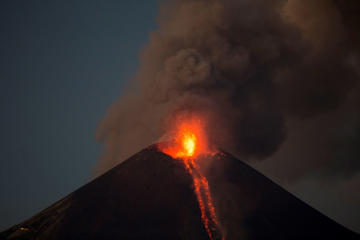The Momotombo volcano spews a large plume of gas and ash as well as glowing rock, as seen from the rural community of Papalonal, in Leon, Nicaragua, Wednesday, Dec, 2, 2015. Quiet for many years, the volcano emitted some glowing rock on Wednesday, after gas and ash emissions began Tuesday. In 1610, the city of Leon was destroyed during an eruption of the Momotombo and was relocated west, where it is currently located.