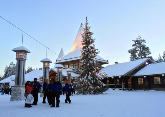 Visitors walk in Santa Claus Village, around 8 kms, 5 miles north of Rovaniemi in Finland on Tuesday Dec. 15, 2015. Most kids learn that Santa Claus comes from the North Pole, but children in Scandinavia are taught he lives a bit further south. Where exactly is a matter of much debate, with businesses in Finland, Sweden and Norway competing to cash in on the cache that comes with claiming Santa's hometown. (AP Photo/James Brooks)