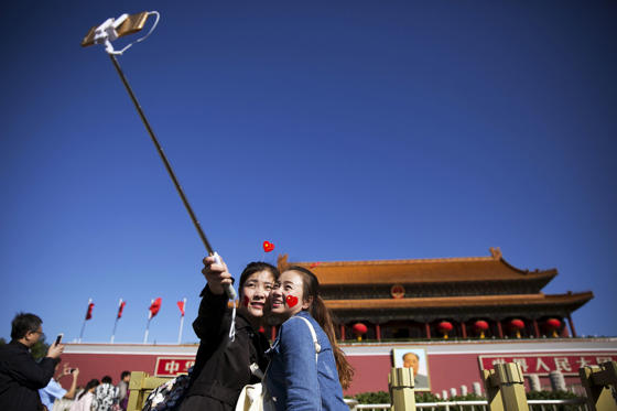 Girls take a selfie at the Tiananmen Gate as they celebrate National Day marking the 66th anniversary of the founding of the People's Republic of China in Beijing