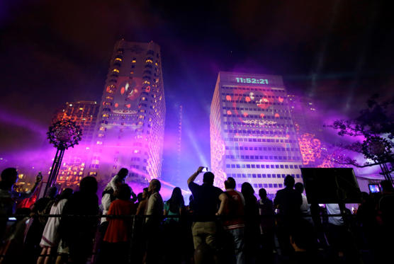 Revelers watch a laser show being projected on buildings as the countdown for the New Year begins in Manila, Philippines Wednesday, Dec 31 2014. Traditionally Filipinos welcome the New Year with firecrackers, fireworks and almost anything to make the loudest noise possible. (AP Photo/Bullit Marquez)