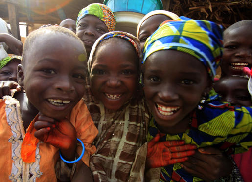 Children smile as they pose in the village of Dawakin Kudu near Kano November 28, 2009. REUTERS/Akintunde Akinleye (NIGERIA SOCIETY)