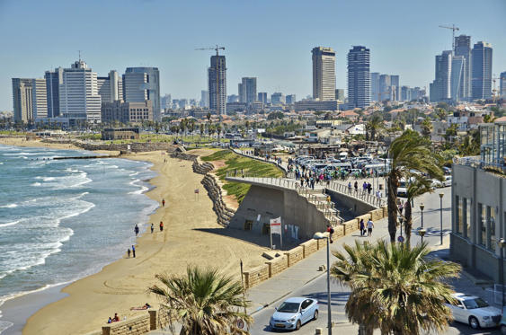 Jaffa, Israel - April 11, 2014: People on the Mediterranean beach and Tel Aviv, Israel boradwalk with the city sky line and towers in the background