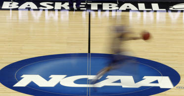 FILE - In this March 14, 2012, file photo made with a long exposure, a player runs across the NCAA logo at midcourt during practice before an college basketball game.
