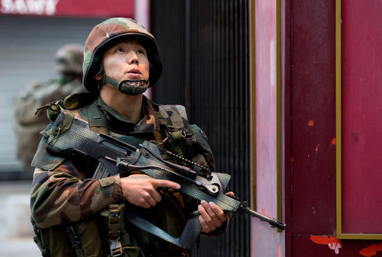 A French soldier takes up position in Paris suburb Saint-Denis, Wednesday, Nov. 18, 2015. Explosions and gunfire rang out as heavily armed police surrounded a suburban Paris apartment in a raid targeting the suspected mastermind of last week's Paris attacks. Peter Dejong/AP
