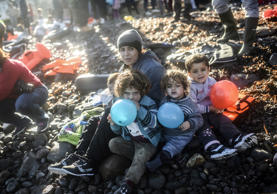 A displaced Iraqi woman from the Yazidi community, who fled violence from Islamic State (IS) group jihadists, sits with her children holding blue and red balloons on the shores of the Greek island of Lesbos after crossing the Aegean Sea from Turkey on November 13, 2015. EU leaders on November 12 struck an aid-for-cooperation deal with Africa and proposed a summit this year with Turkey in a two-front push with wary partners to tackle an unprecedented migrant crisis.