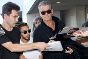 Actor Pierce Brosnan, right, is surrounded by people seeking an autograph on Nov. 6, 2014, at Los Angeles International Airport.