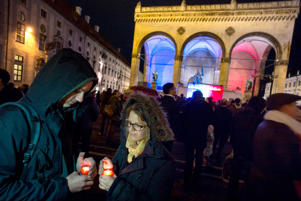 People in Munich hold candles during a memorial service for the victims of the attacks in Paris on Nov. 19, 2015.
