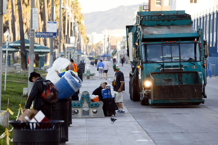 people sit as sanitation workers empty trash cans during morning cleanup of homeless encampments on the Venice Beach boardwalk in Los Angeles, California, U.S., on Friday, Oct. 9, 2015.