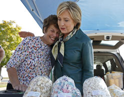 U.S. Democratic presidential candidate Hillary Clinton hugs a vendor as she shops at a farmer's market in Davenport, Iowa October 6, 2015. Jim Young/Reuters