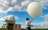 National Weather Service meteorologist intern Gordon Strassberg prepares to launch a weather balloon equipped with a radiosonde device Tuesday, May 16, 2006, at the NWS station in Topeka, Kan. Nick Krug/The Lawrence Journal-World/AP