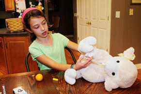 Audrey Stepp, 8, practices injecting a heroin antidote, naloxone, into her stuffed lamb Bill, at home in Sherpherdsville, Kentucky, Nov. 18, 2015. Audrey is being trained how to inject Naloxone using a kit with a preloaded syringe similar to an Epi-pen, along with a regular syringe and a nasal injection method.