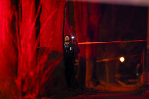 A Minneapolis police officer investigates the site of Monday night's shooting in...