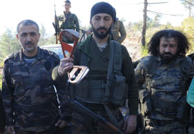 Alpaslan Celik, a deputy commander in a Syrian Turkmen brigade (C), holds handle...