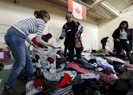 Clothing donated for an expected influx of Syrian refugees is sorted by voluntee...