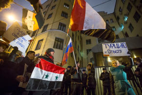 Protesters hold Russian and Syrian national flags and posters reading 'Turkey to account!' , right, and 'Stab in the back - a response in the face!' , left, during a picket at the Turkish Embassy in Moscow, Russia, Tuesday, Nov. 24, 2015.