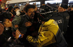 A demonstrator scuffles with a police officer after protests broke out in Chicag...