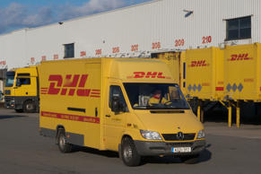 A delivery truck passes DHL shipping containers at a package sorting center in C...