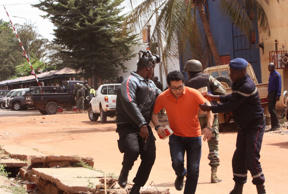 In this Friday, Nov. 20, 2015 file photo, Mali troopers assist a hostage to leave the Radisson Blu hotel to safety after gunmen attacked the hotel, in Bamako, Mali. The al-Qaida-claimed attack on a Mali hotel may have been partly aimed at asserting the global terror network's relevance as it faces an unprecedented challenge from the Islamic State group for leadership of the global jihadi movement.