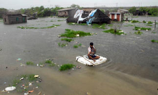 File: A man paddles a makeshift boat on a flooded road in the southern Indian city of Chennai November 29, 2008.
