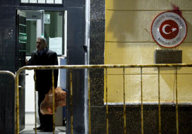 A man walks out of the Turkish embassy next to a sign that was stained by protes...