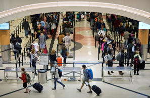 Travelers wait to go through a security checkpoint at Hartsfield–Jackson Atlanta...