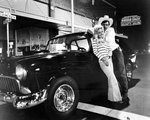 Bob Falfa, played by American actor Harrison Ford, with a girlfriend and his 1955 Chevrolet in 'American Graffiti', directed by George Lucas, 1973.