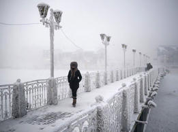 A woman walks over an ice-encrusted bridge in Yakutsk